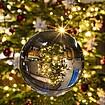 Weihnachtsbaum durch eine Glaskugel hindurch betrachtet.